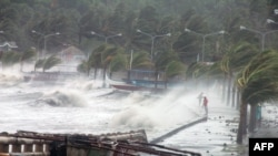 A resident walks past high waves pounding the sea wall amid strong winds as Typhoon Haiyan makes landfall in the Philippines.