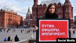"""Putin. Offshore, Impeachment."" -- A lone protester holds up a sign in Moscow protesting over the fact that Russian President Vladimir Putin is seen to have been implicated in murky financial dealings revealed in the Panama Papers"
