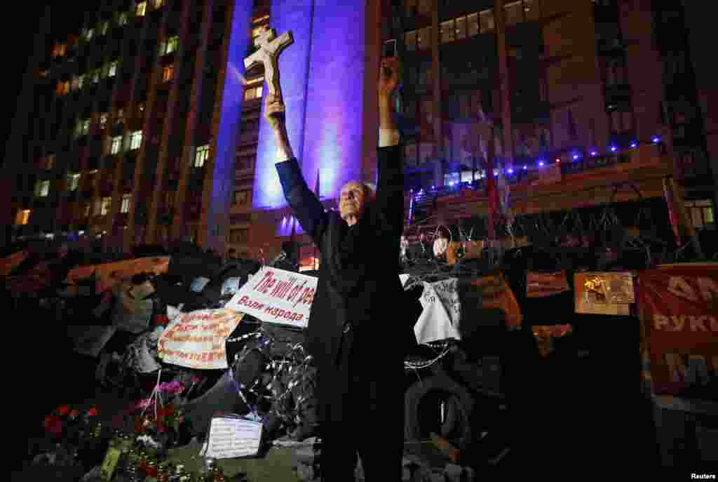 A man holds a cross and a telephone as he stands near a barricade erected by pro-Russian activists during a rally to mark and celebrate the announcement of the results of the referendum on the status of Donetsk region in Donetsk on May 12. (Reuters/Maksim Zmeyev)