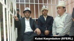 Opposition deputies Kamchybek Tashiev, Sadyr Japarov, and Talant Mamytov (left to right) in the dock at the start of their trial in Bishkek on January 10.