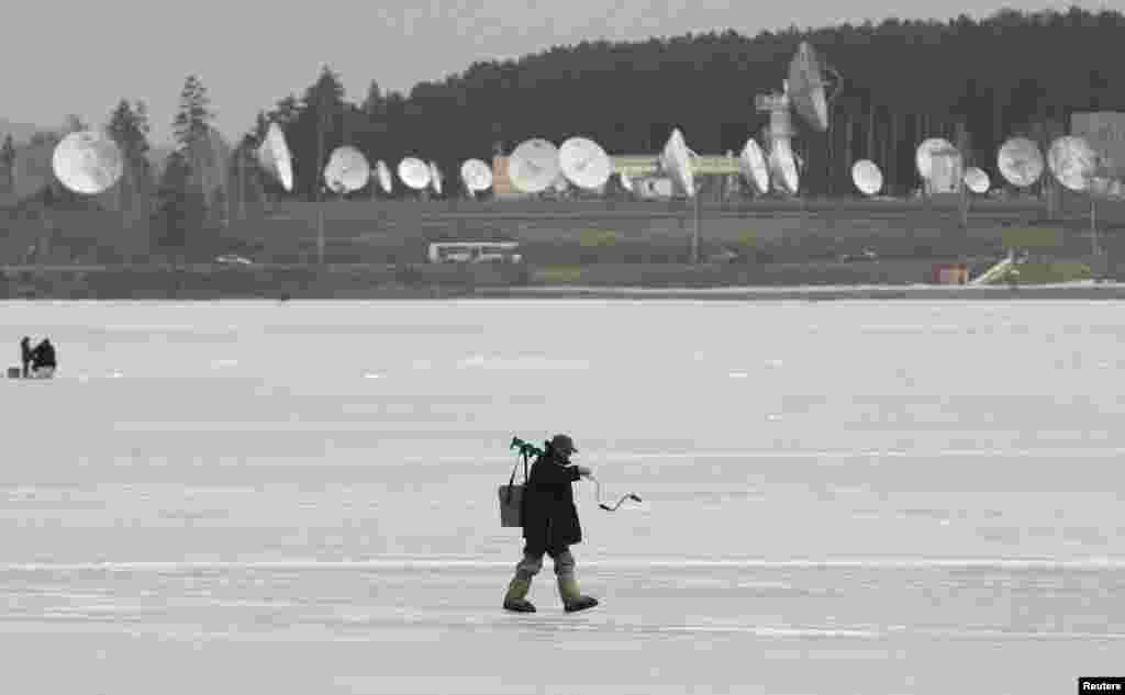 A fisherman walks on the frozen surface of a lake, with satellite dishes of a local space communication center seen in the background, in the town of Zheleznogorsk, Russia. (Reuters/Ilya Naymushin)