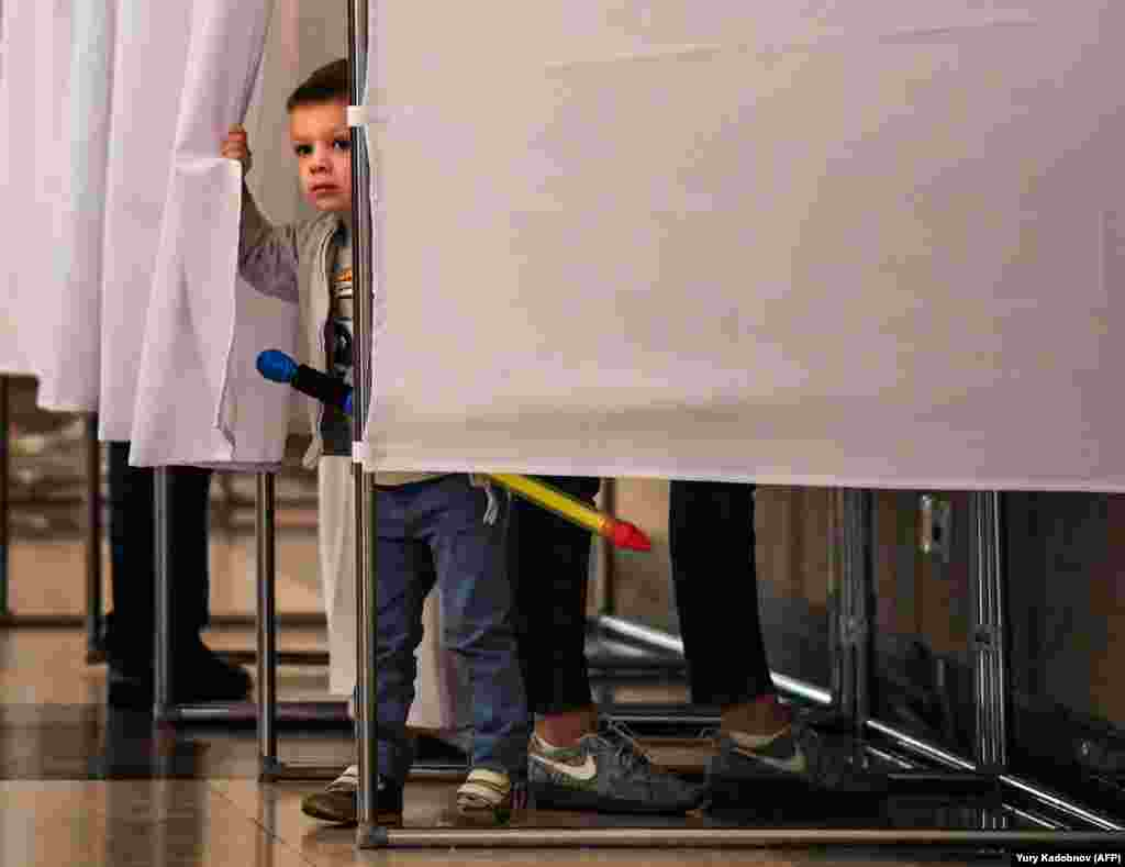 A boy peeps out from behind the curtains of a voting booth at a polling station during the municipal elections in Moscow on September 10. (AFP/Yury Kadobnov)