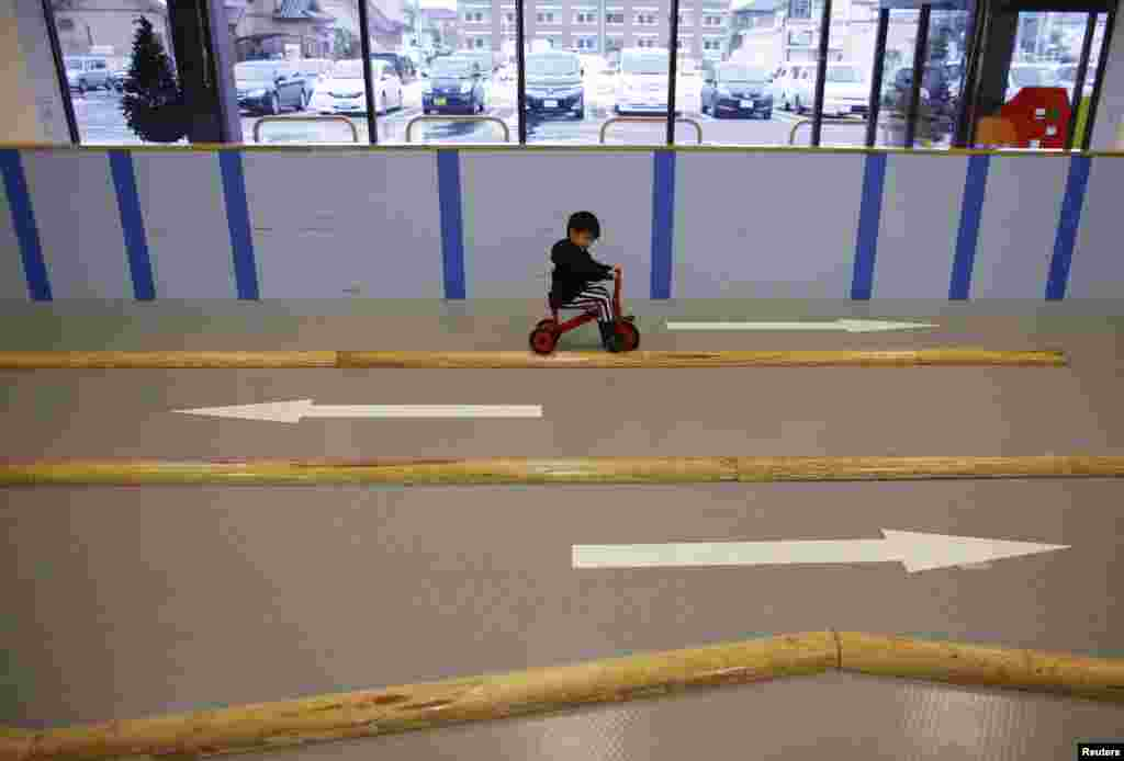 Four-year-old Iori Hiyama rides a tricycle at an indoor playground.