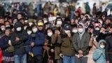 Толпа, собравшаяся на улице, пытается разглядеть церемонию передачи олимпийского огня. Токио, 20 марта