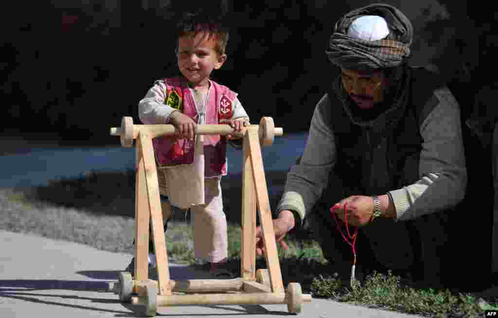 A 3-year-old child patient who lost his leg in a suicide attack in Kandahar walks with the aid of a stroller at the International Red Cross Center in Kabul. (AFP/Jawad Jalali)