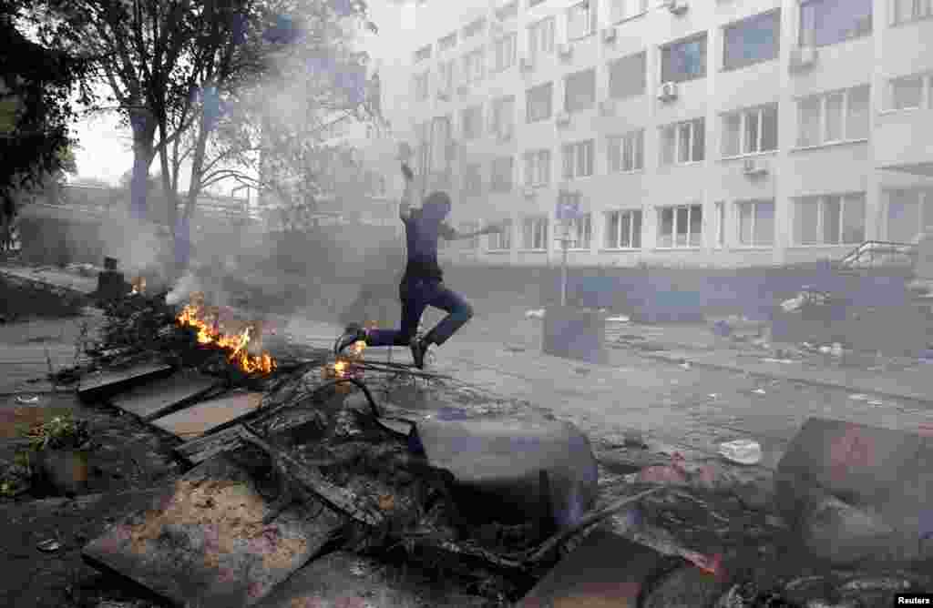 A masked man jumps over a burning barricade in front of the police headquarters in the southeastern Ukrainian port city of Mariupol on May 9. (Reuters/Marko Djurica)