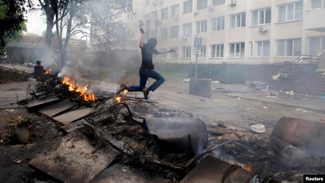 A masked man jumps over a burning barricade in front of police headquarters in the embattled southeastern port city of Mariupol on May 9.