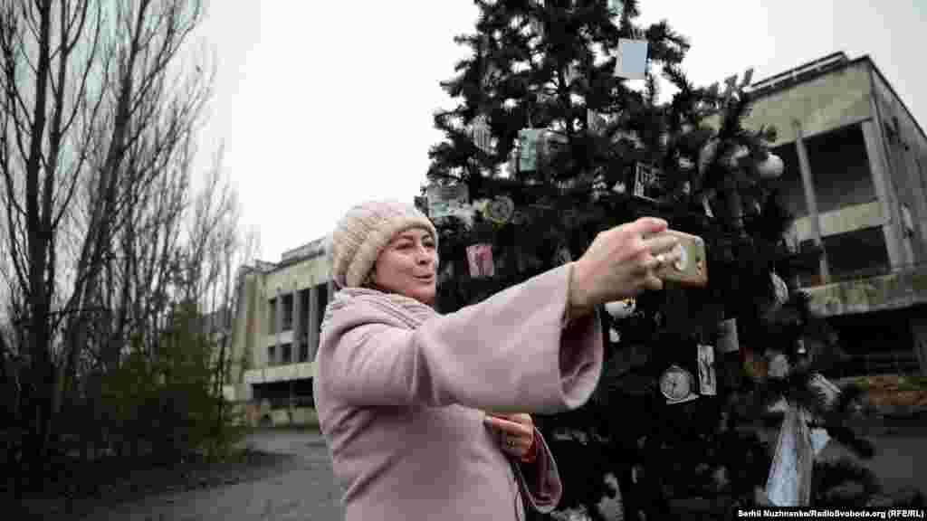 Бывшая жительница Припяти Елена Панцюк снимает видео для своих одноклассников около елки на площади «города-призрака»