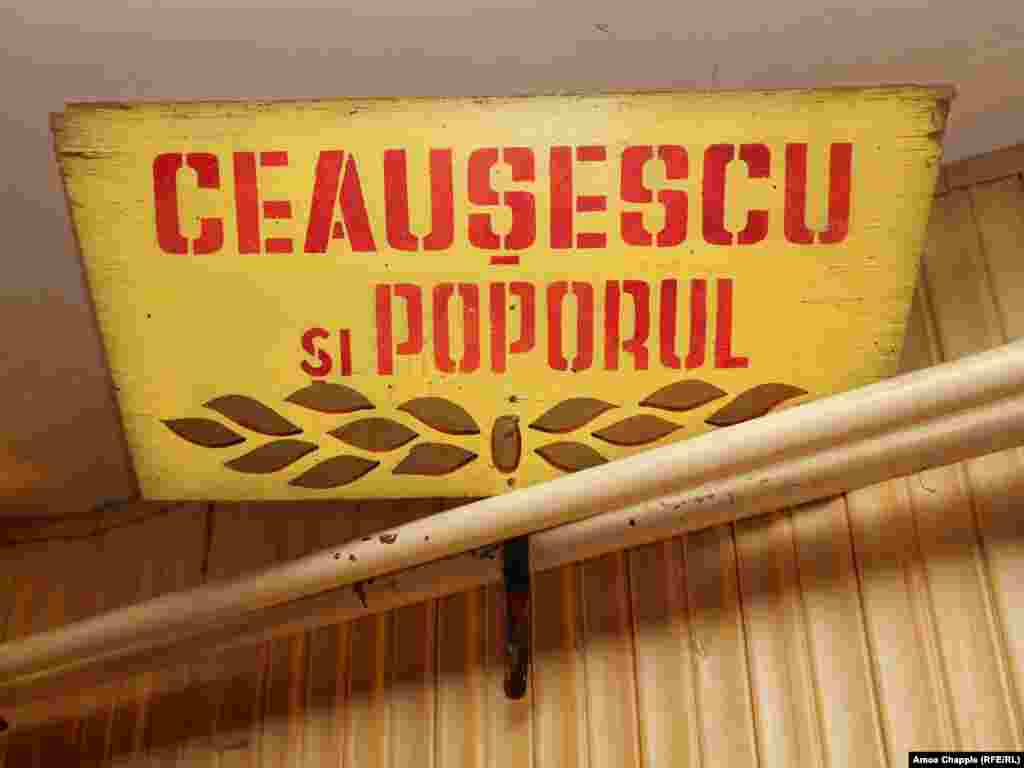 "A sign reading ""Ceausescu and the people,"" a common slogan of the era. Mihaita told RFE/RL that after the communist regime was overthrown, Romanians were eager to destroy relics linked to the hated ruler. ""I remember in the '90s, in the schools we would throw pictures of Ceausescu out the windows. We wanted to physically get rid of the past."""