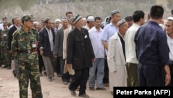 FILE: Ethnic Uighurs, some wearing white flowers, gather before an official ceremony.