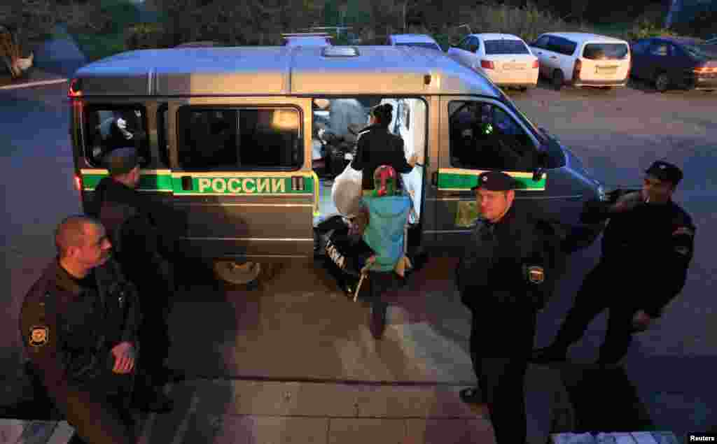 Migrants board a police van before being deported from Russia.