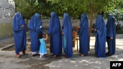 Afghan women voters line up to cast their ballots in Jalalabad on June 14 in the second round of a presidential election that has been marred by fraud allegations.