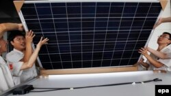 Қытайлық жұмысшылар күн батареясын орнатып жатыр. 2 тамыз 2012 жыл