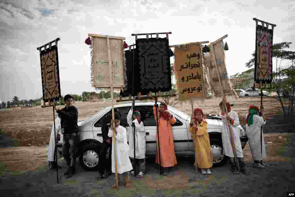 Children hold banners during a Ta'zieh performance.
