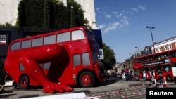 A London bus that has been transformed into a robotic sculpture by Czech artist David Cerny is assembled in front of the Czech Olympic headquarters in London.