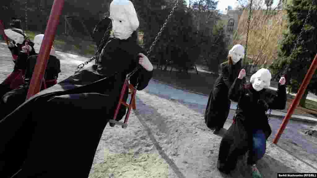Актори в костюмах Миколи Гоголя під час акції бавляться на гойдалках