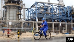 A worker rides a bicycle through the Nouri Petrochemical facilities of the South Pars gas field, which the planned pipeline would link with consumers in South Asia.