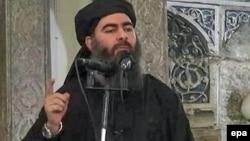 На кадре пропагандистского видеообращения ИГ предположительно Абу Бакр аль-Багдади, известный как лидер ИГ и халиф самопровозглашенного исламского халифата.