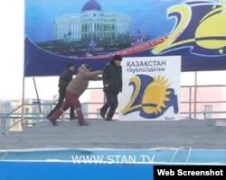 "Мужчина толкает полицейского на сцене на площади в Жанаозене. 16 декабря 2011 года. Скриншот с видеопортала ""Стан.кз"""