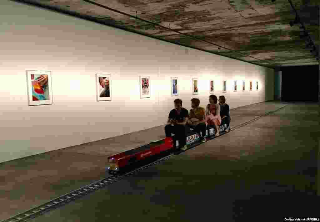 Джозефина Прайд фотографирует руки (как правило, с маникюром). Она предлагает зрителям взгромоздиться на поезд и прокатиться вдоль стены, где выставлены ее снимки.