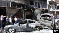 People look at burned-out car bombs after an attack that killed at least 10 people and wounded 62 in the Jaramanah suburb in southeast Damascus on July 25.