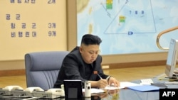 North Korean leader Kim Jong Un at an undisclosed location, sitting in front of a map that appears to show the tracked or projected movement of the U.S. Seventh Fleet in the Pacific Ocean