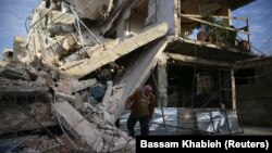 A person inspects damaged building in the besieged town of Douma, Eastern Ghouta, Damascus, Syria February 20, 2018.