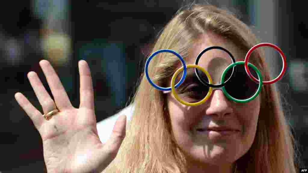 A woman wearing sunglasses featuring the Olympic rings cheers during the torch relay on July 26. (AFP/Miguel Medina)