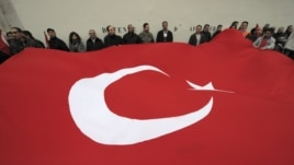 France -- Franco-Turk protesters hold a giant Turkish flag during a demonstration next to the National Assembly in Paris, 22Dec2011