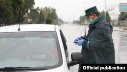 Сотрудник ГАИ проверяет документы во время карантина в Ташкенте.