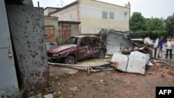 Місцеві жителі біля знищеного під час боїв автомобіля, Луганськ, 19 липня 2014 року