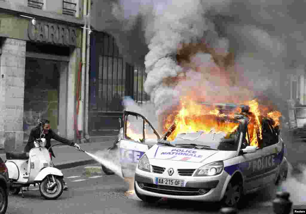 A police car burns during a demonstration against police violence and French labor reform in Paris on May 18. (Reuters/Charles Platiau)