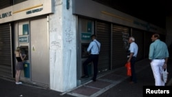 Афіни, ніч на 17 липня 2015 року: черги перед банкоматами під закритим банком і написи «€ = 卐»
