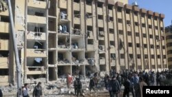 Security personnel and civilians gather at the site where two explosions rocked Aleppo University.