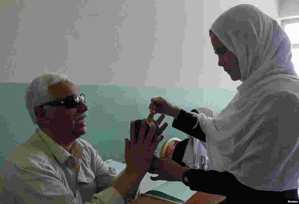 A teacher, who is also blind, teaches students at the school.