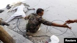 Боец Свободной сирийской армии волочит мертвое тело погибшего в Алеппо. 13 августа 2012 года.