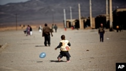 An Afghan child plays with a baloon at the Shahid Nasseri refugee camp in Taraz Nahid village near the city of Saveh, some 130 kms southwest of the capital Tehran, on February 8, 2015. Some 5000 Afghan refugees live at the camp which is run by the Iranian