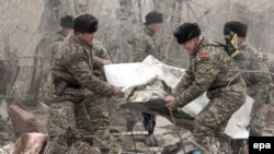 Kyrgyz servicemen carry a body bag with a victim at the crash site of a Turkish cargo plane in the village of Dacha-Suu outside Bishkek, which killed 28 people earlier this week.