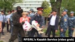 Полицейский спецназ тащит предполагаемую участницу акции с требованием «освободить политзаключенных» и «прекратить пытки». Алматы, 10 мая 2018 года.