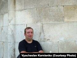 Історик В'ячеслав Корнієнко біля графіті на стіні (зовнішній) храму святого Пантелеймона