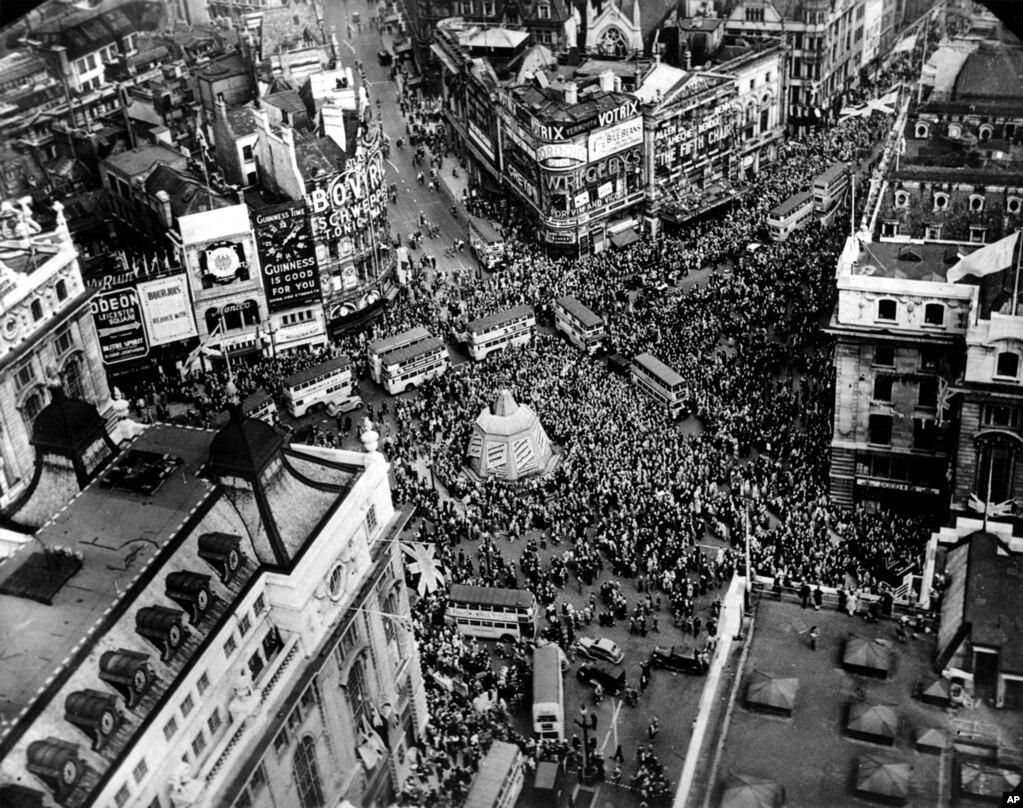 Натовп на площі Пікаділлі в Лондоні, 8 травня 1945 року. У центрі площі – ще закритий камуфляжем від нацистських бомбардувань меморіальний фонтан Шефтсбері, вірніше, основа фонтану, бо сам історичний пам'ятник був розібраний і поміщений в укриття. Фонтан повернувся на площу тільки в 1948 році