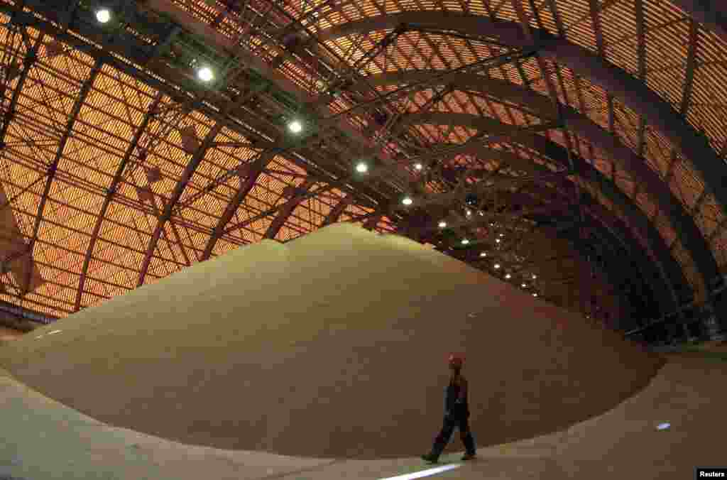 An employee at an above ground pile of processed potassium salts at a Uralkali potash mine.