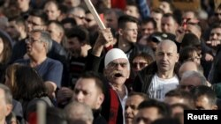 Demonstrators shout antigovernment slogans during a protest in Pristina on February 17.