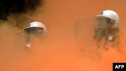 Greek riot policemen stand in smoke during clashes with demonstrators in front of the parliament in Athens on June 29.