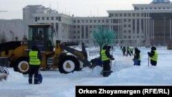 Астананың орталығында қар тазалап жүрген жұмысшылар (Көрнекі сурет).