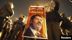 Президент Мұхаммед Мурсидің жақтастары оның суретін ұстап, акция өткізіп тұр. Каир, 9 желтоқсан 2012 жыл.