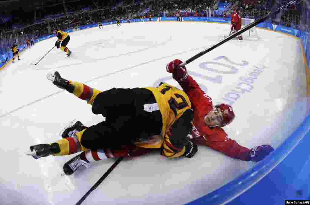 Ice Hockey Men: Brooks Macek (12), of Germany, collides with Russian athlete Bogdan Kiselevich (55) during the third period of the men's gold medal hockey game at the 2018 Winter Olympics, Sunday, Feb. 25, 2018, in Gangneung, South Korea. (AP Photo/Julio Cortez)