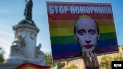 "A demonstrator holds a placard depicting Russian President Vladimir Putin with the label ""Stop Homophobia"" to denounce the antigay campaign launched in the Russian region of Chechnya during a protest held in Paris on April 20."