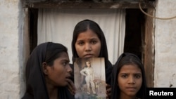 The daughters of Christian woman Asia Bibi pose with an image of their mother while standing outside their residence in Sheikhupura in the eastern Punjab Province.