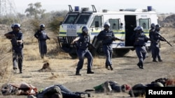 Вооруженные полицейские стоят напротив тел убитых и раненых шахтеров. Рустенберг, 100 км от Йоханнесбурга, столицы ЮАР. 16 августа 2012 года.